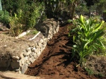 Permaculture swale improvements by rockwall, result in improved garden beds with better edging.