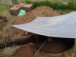 A tarp placed over the hole to keep out the rain. Bricks to be used for the walls in the background.