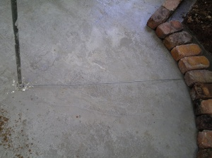 Wire attached to pole to measure inner and outer circle, so the bricks would end up on top of the thicker concrete