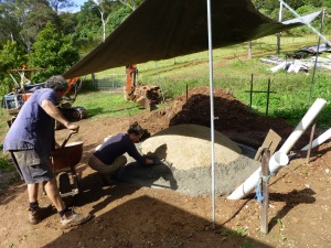 Concrete is poured and worked on top of the biodigester's soil dome base.