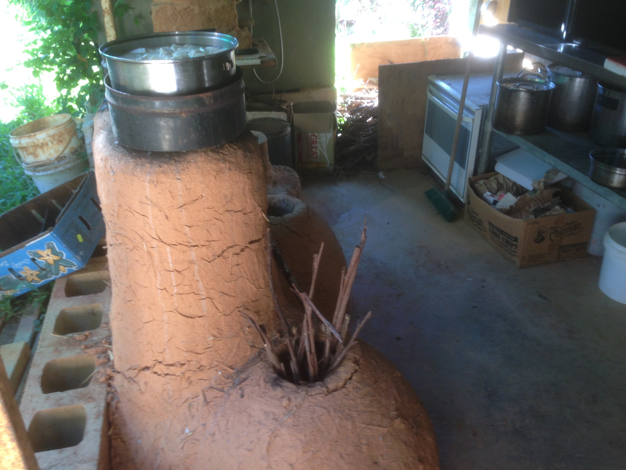Tom Kendall uses a rocket stove to cook cassava at Maungaraeeda.