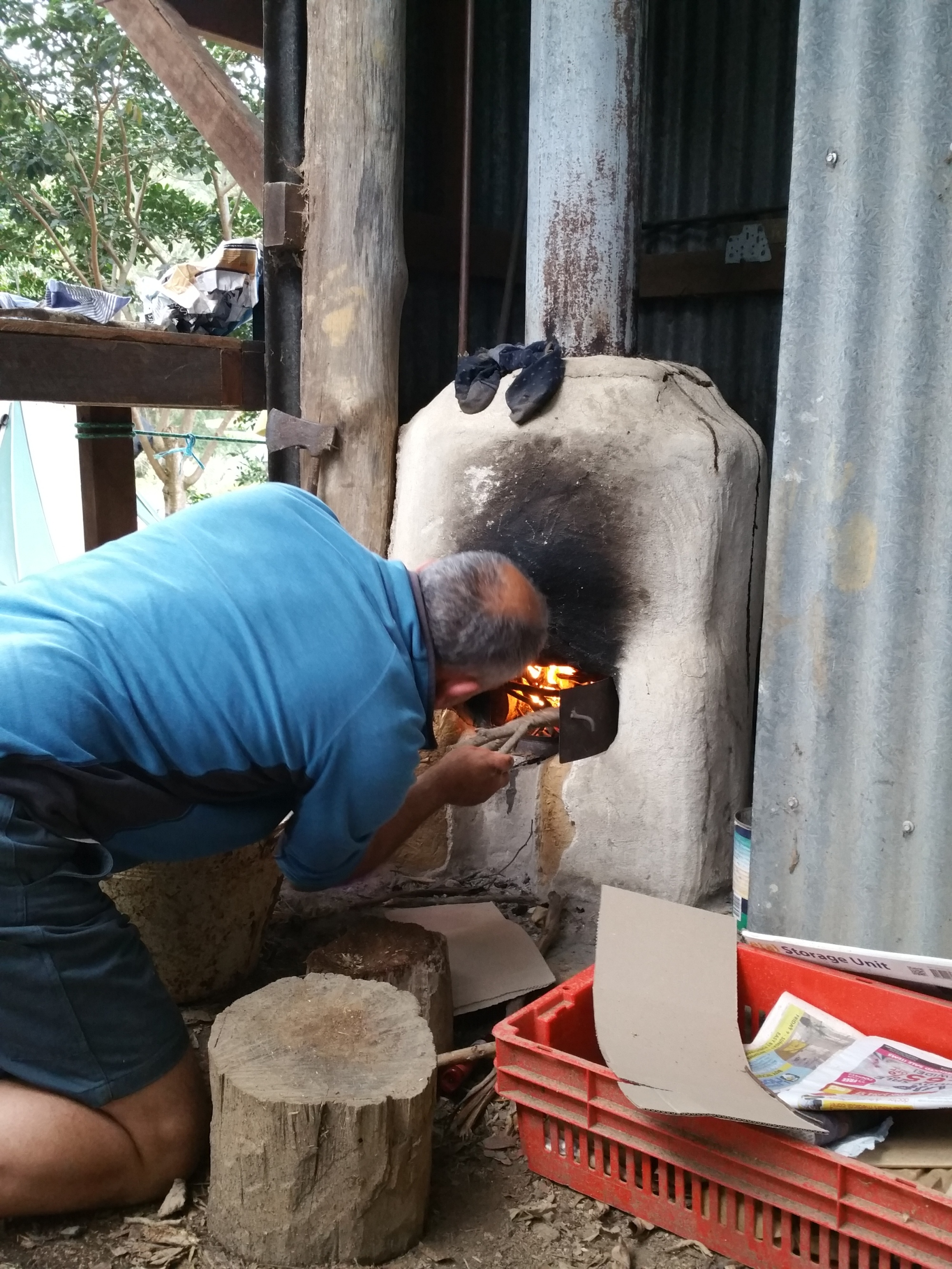 Lighting the water heater fire during the PDC course at the Permaculture Research Institute Sunshine Coast